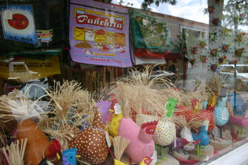 Colorful Mexican handbags and raffia-tailed chickens throng the window at the Davis Mather Folk Art Gallery.