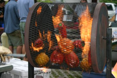 At the Carrboro Farmer's Market, a mix of hot and sweet capsicums from Peregrine Farm are roasted over flames in a hand-cranked propane-fired wire drum.