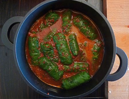 The chard dolma are simmered in water mixed with a vibrant red pepper paste from southeastern Turkey.