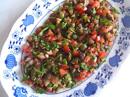 A tangy olive salad, mixed with tomato, scallions and parsley, dressed with pomegranate molasses, olive oil and lemon juice.